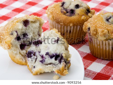 A freshly baked blueberry muffin with struesel topping for breakfast. Two other muffins in background.
