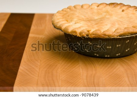A freshly baked chicken pot pie sitting on an attractive wooden cutting board. Selective focus on front edge of pot pie.