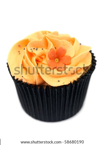 A freshly baked cup cake with orange frosting