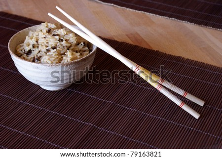 A freshly cooked bowl of rice with wooden chopsticks to enjoy a taste of the orient.