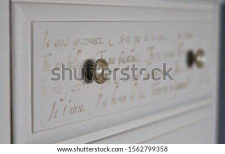 A freshly finished chest of drawers, refurbished and refinished, and detailed with cursive scripts, designs,and transfers.