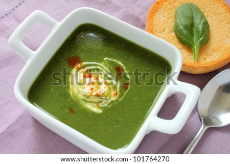 A freshly made bowl of spinach soup on a linen placemat.