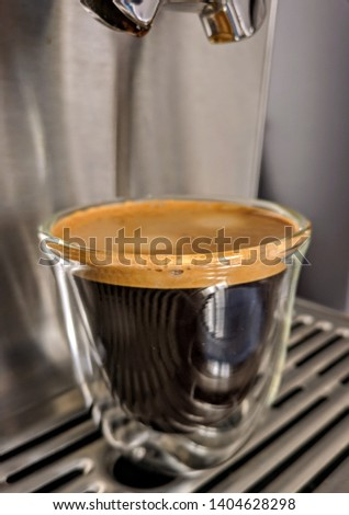 A freshly made espresso in an espresso glass on an espresso machine with thick rich crema #1404628298