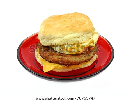A freshly made sausage egg and cheese breakfast sandwich on a red plate.