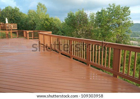 A freshly painted and stained wood deck with railing on a summer afternoon after a rain shower.