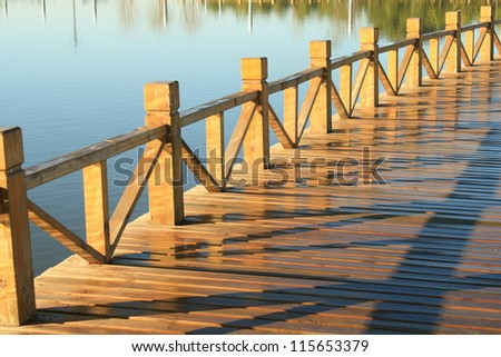 A freshly painted and stained wood deck with railing on autumn morning after a rain shower.