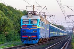 A freshly painted blue electric locomotive pulls a passenger train along a railway line. Summer shot.