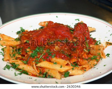 a freshly prepared dish of ziti with chunky tomato sauce in the kitchen of an italian restaurant