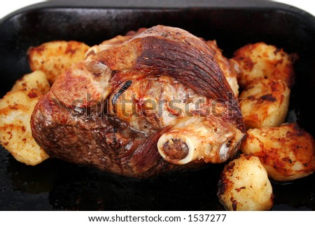 A freshly roasted leg of lamb with potatoes isolated in a baking tray