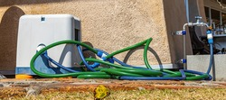 A freshly used, green, water hose is discarded against the wall of a restaurant, on a very sunny and hot day.