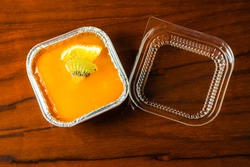 A freud box of orange fruit custard cake which a piece of kiwi and orange are on top over jelly layer. Box cover is placed near. It is on brown wood table. Stay at home in COVID-19 pandemic.