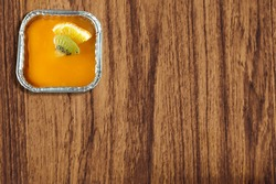 A freud box of orange fruit custard cake which a piece of kiwi and orange are on top over jelly layer. It is isolated on brown wood texture. Stay at home in COVID-19 pandemic. Copy space.