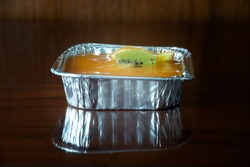 A freud box of orange fruit custard cake which a piece of kiwi and orange are on top over jelly layer. It is on brown wood table. Stay at home in COVID-19 pandemic.