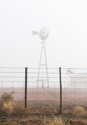 A fridgid foggy day enhances a barbered fence that frames a windmill
