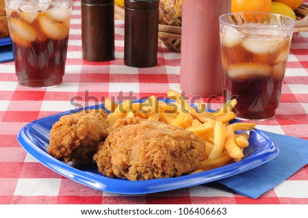A fried chicken picnic lunch with potato chips and cola
