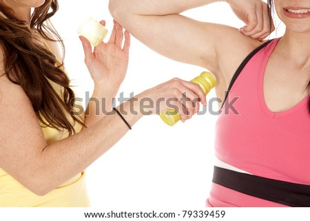 a friend helping her friends put some underarm deodorant on her armpit.