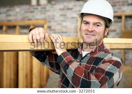 A friendly appealing construction worker in classic pose, carrying planks on the jobsite.  Model is actual construction worker. Authentic and accurate content depiction.