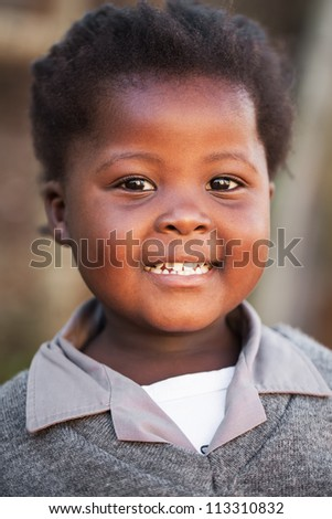 A friendly face is greeting the photographer in the street after school.