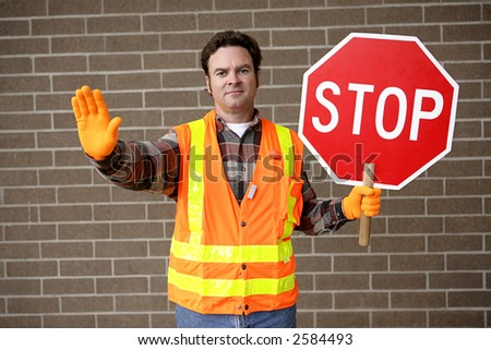 A friendly school crossing guard holding a stop sign. - stock photo