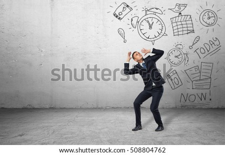 A frightened businessman shielding himself with his hands from the drawings of calendars and clocks on the grey wall. Business and time-management. Organizing and planning. Productivity and efficiency