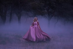 A frightened girl blonde runs away from a forest that has covered a thick fog. On the elf, a luxurious pink dress with a long train and a raincoat. Artistic photo.