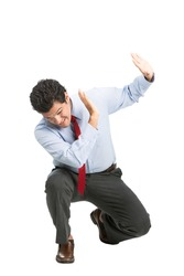 A frightened hispanic male office worker in business clothes, head down, crouching putting up hands shielding in self defense under attack. Workplace violence isolated on white