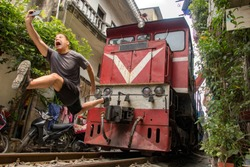 A frightened tourist makes dangerously selfie photo in front of moving train. An undisciplined traveler in the popular Hanoi railway street, Vietnam.