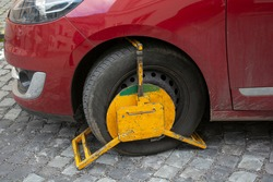 A front car wheel blocked by wheel lock for unauthorized or illegal parking. A wheel clamp also known as wheel boot or  parking boot.