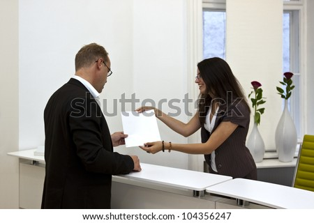 A front desk lady doing her job very well and cheerfully while she's consulting a customer.  The white space on the sheet of paper could be used for any graphic additions. - stock photo