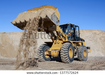 A front end loader machine tipping sand in a quarry #1377572624