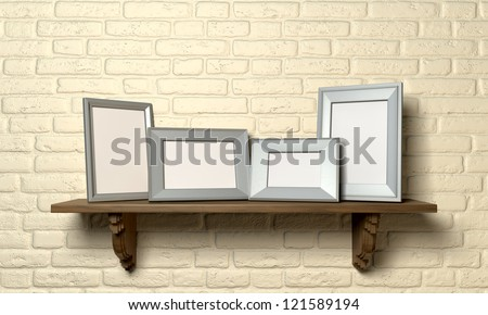 A front view of a regular wooden shelf displaying 4 blank metal picture frames on a yellow brick wall