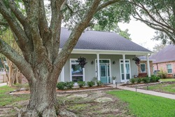 A front view of an Acadian renovated home with columns, sidewalks and a colorful front door recently purchased with the changing real estate market.