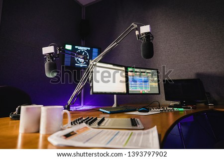 A front view shot of a radio station studio interior, a large desk is in the middle of the room, recording equipment and computers can be seen on the desk. #1393797902