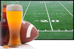 A frothy glass of beer with an American Football in front of a big screen television. Great for Super Bowl themed projects.