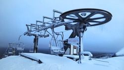 A frozen and abandoned Chairlift in the snowy mountains. A devastated ska lift covered with snow and frost with a red inscription