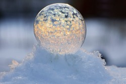 A frozen bubble in the snow with bokeh in the background. Beautiful frosty patterns on a frozen soap bubble. winter, frosty background. Frozen bubble at sunset light. soap bubble on snow close up