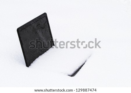 A frozen laptop computer half buried in  snow drift