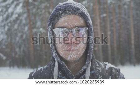 a frozen man with glasses in the snow looks at the camera in the winter forest after a snow storm #1020235939