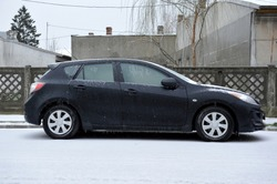 A frozen Mazda 3 car on the frozen streets of Popesti Leordeni, Bucharest, Romania. On the background you can see an old communist fence.