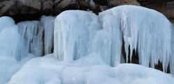 A frozen waterfall has formed as water from the spring in the rocks above has seeped down and frozen into a sculpture of icicles and sheets of opaque blue ice.