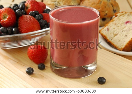 A fruit smoothie with cranberry bread and muffins