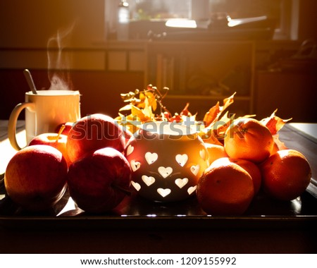 A fruit tray with apples and oranges, a cute candle holder, fall leaves, twigs of berries and a steaming mug of tea on the side. Warm sunlight streaming in from the window. A picture of autumn colors.
