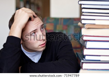 A frustrated and stressed out student looks up at the high pile of textbooks he has to go through to do his homework.