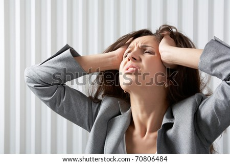 A frustrated businesswoman disarranging her hair