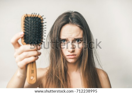 A frustrated girl holds a comb with hair falling out in her hand, looks into the camera