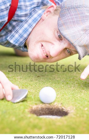 A Frustrated Yet Funny Golfing Fanatical Man Points At His Golf Ball While Hurling A Barrage Of Insults In A Comical Image Representing Golf Lunacy