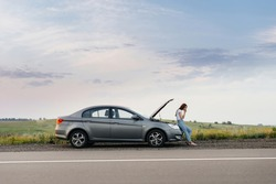 A frustrated young girl stands near a broken-down car in the middle of the highway during sunset. Breakdown and repair of the car. Waiting for help.