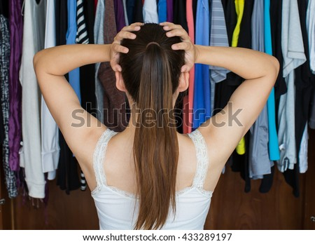 A frustrated young woman standing in front of her closet, trying to decide on her best outfit for a night out with her friends. #433289197