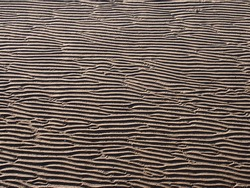 A full frame beach background with wavy pattered surface formed by water on the wet sand and shadow