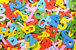 A full frame closeup shot of various english alphabet cutouts from wood and painted in multicolours.